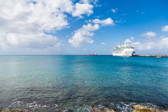 White Cruise Ship Docked Beyond Surf. White Luxury Cruise Ship Docked at St Croix Stock Image