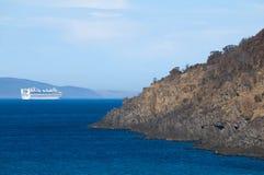 White cruise ship with rocky headland stock photo