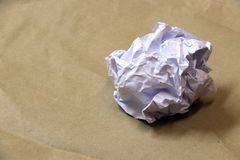 White crumpled paper ball on the brown paper floor. stock images