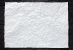 White crumpled paper on dark wood Stock Photos