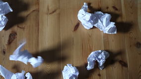 White crumpled paper falling on wooden floor. White crumpled paper falling on a wooden floor stock video footage