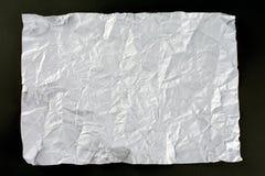 White crumpled sheet of paper. Dark gray background stock photo