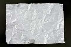 White crumpled sheet of paper. Dark gray background stock images