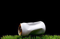 A white crushed soda can tossed on grass Royalty Free Stock Image