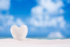 White crystal heart on white sand beach Royalty Free Stock Image