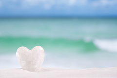 White crystal heart on white sand beach Royalty Free Stock Photography