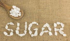 White crystalline sugar arrange as word sugar  on brown Royalty Free Stock Photo