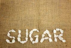 White crystalline sugar arrange as word sugar  on brown Royalty Free Stock Photos