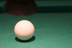 White cue ball on pool table. Closeup of a white cue ball on a pool table Stock Photo