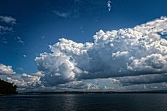 White Cumulus cloud in blue sky at sea. Stock Images