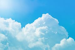 White cumulus clouds against a bright blue sky. White cumulus fluffy clouds against a bright blue sky and sun background, toned stock images