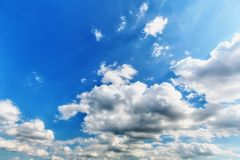 White cumulus clouds. Background of white cumulus clouds with sunlight in the blue sky stock image