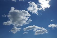 White Cumulus clouds on a blue sky background. Fluffy, fancy shape royalty free stock photo