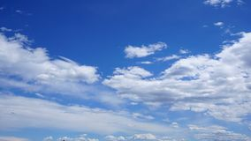 White cumulus clouds in blue sky. Spring time stock photo