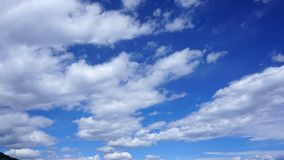White cumulus clouds in blue sky. Spring time royalty free stock image