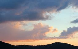 White cumulus clouds of interesting shape and mountain. White cumulus clouds of interesting forma and mountain, sunset and blue sky, clouds float from behind the stock image