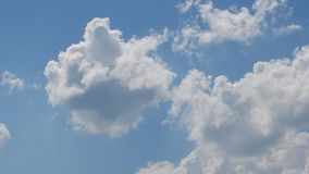 White cumulus clouds moving fast in blue sky - time lapse. Spring time stock video