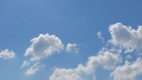 White cumulus clouds moving fast in blue sky - time lapse. Spring time stock video footage