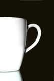 White cup. On a mirror in front of a black background Royalty Free Stock Photography
