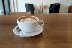 A white cup of beautiful hot cocoa on wooden table and blur back Royalty Free Stock Photo