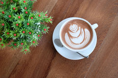 A white cup of beautiful hot cocoa on wooden table Stock Photos