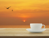 White cup with birds on wooden table over sunset sky Royalty Free Stock Images