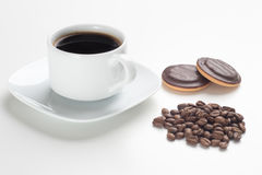 White cup, black coffee, beans and cakes Stock Image