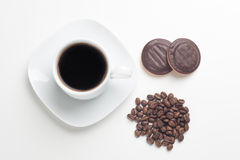 White cup, black coffee, beans and cakes Stock Photography
