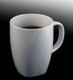 White cup of black coffee on black graded background. A white cup of black coffee on black graded background royalty free stock photos