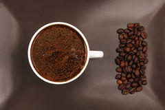 White cup of black coffee on a brown plate with coffee beans Royalty Free Stock Image