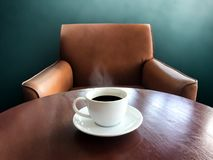 White cup of black coffee on brown wood table with cozy armchair Royalty Free Stock Image