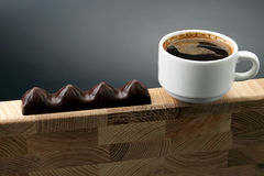 White Cup of black coffee with chocolate on a wooden frame Royalty Free Stock Photo