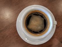 A white cup of black coffee with creama put over brown wooden table. The white cup of black coffee with creama put over brown wooden table Royalty Free Stock Photography