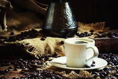 White cup of black coffee with foam, Turkish coffee maker on the. Old wooden table on canvas napkin, vintage toned image, selective focus stock images
