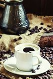 White cup of black coffee with foam, Turkish coffee maker on the. Old wooden table on canvas napkin, vintage toned image, selective focus royalty free stock image
