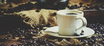 White cup of black coffee with foam, Turkish coffee maker on the. Old wooden table on canvas napkin, vintage toned image, selective focus and toned image stock photos