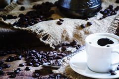 White cup of black coffee with foam, Turkish coffee maker on the. Old wooden table on canvas napkin, vintage toned image, selective focus royalty free stock photo
