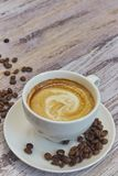 White cup with black coffee with milk. Handful of coffee beans on a wooden table. vertical view of drink with coffee. Copy space royalty free stock images