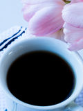 White cup of black coffee with pink tulip on  white background Stock Image