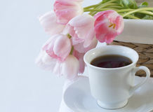 White cup of black coffee with pink tulip on  white background Stock Photos