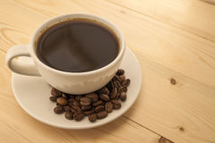White cup with black coffee on plate with coffee beans on yellow Royalty Free Stock Photography