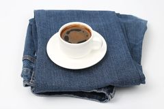 White Cup of black coffee rests on denim pants. The white Cup of black coffee rests on denim pants Stock Photography