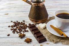 A white cup with black coffee on sacking, anise, sugar, a piece of chocolate, coffee beans and cinnamon sticks on bright wooden ta Royalty Free Stock Image