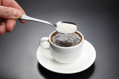 White cup with black coffee and spoon with sugar Stock Photos