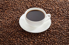 White cup of black coffee standing on roasted coffee beans. Royalty Free Stock Image