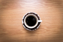 White cup with black, hot coffee standing on brown, roasted beans on wood table. Royalty Free Stock Images
