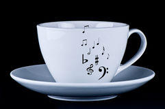 White cup with black musical notes. Black background stock photo