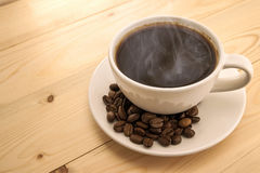 White cup with black steaming coffee on plate with coffee beans Royalty Free Stock Images