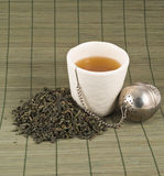 White cup of black tea. With the heap of tea over bamboo mat Royalty Free Stock Photography