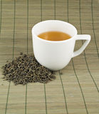 White cup of black tea. With the heap of tea over bamboo mat Royalty Free Stock Images